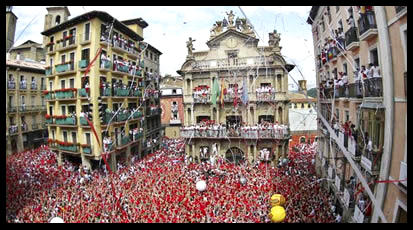 Revellers hold up traditional red scarves in front of Pamplona¿s town hall square during the start of the San Fermin festival